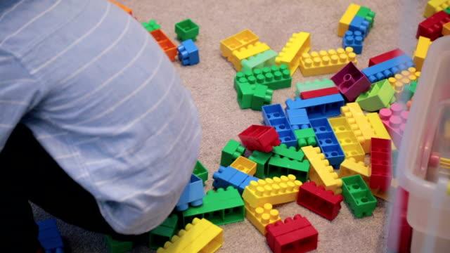 jungen im kindergarten mit klötzchen spielen - teppich stock-videos und b-roll-filmmaterial