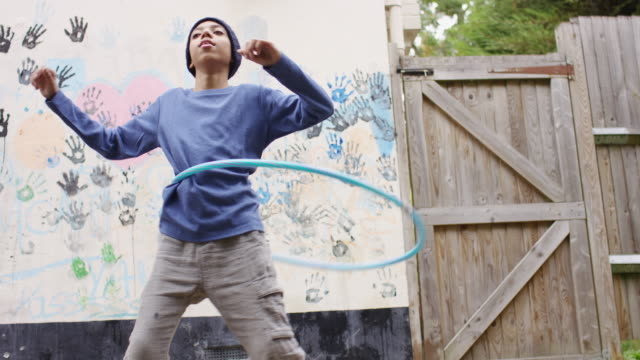 vídeos de stock e filmes b-roll de boy in knit hat dancing in backyard with his hula hoop - inclinar se pose