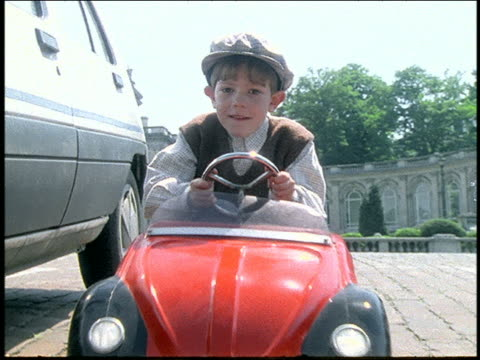 boy in miniature car parking between 2 real cars in parking lot - londonalight stock videos and b-roll footage