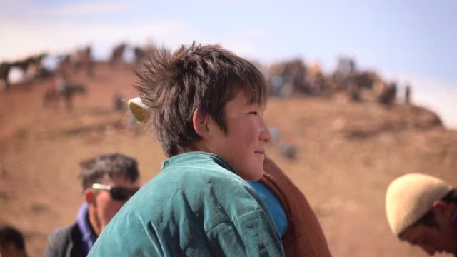 vídeos de stock, filmes e b-roll de boy in mongolia at golden eagle festival - montar um animal