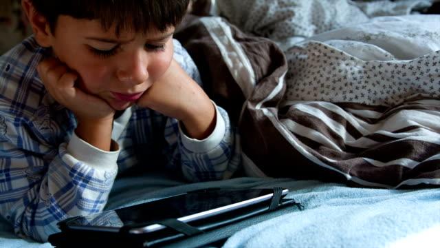 Junge im Schlafanzug im Bett mit tablet Lächeln