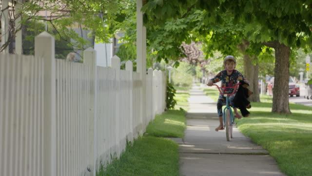 vídeos y material grabado en eventos de stock de boy in pajamas riding bicycle on neighborhood sidewalk / provo, utah, united states - provo