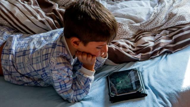 Junge im Schlafanzug mit einem tablet