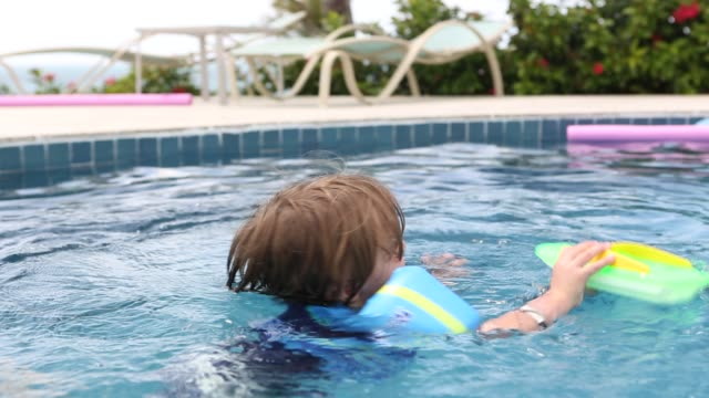 boy in pool - schwimmflügel stock-videos und b-roll-filmmaterial