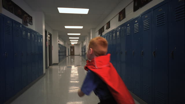 SLO MO MS Boy (5-6) in red hero cape running away from camera, Oshkosh, Wisconsin, USA