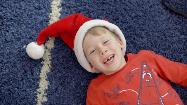 junge in rotem weihnachtsmann-hut. - draufsicht stock-videos und b-roll-filmmaterial