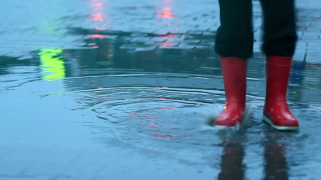 stockvideo's en b-roll-footage met boy in rubber boots leaps over a puddle - rubberlaars