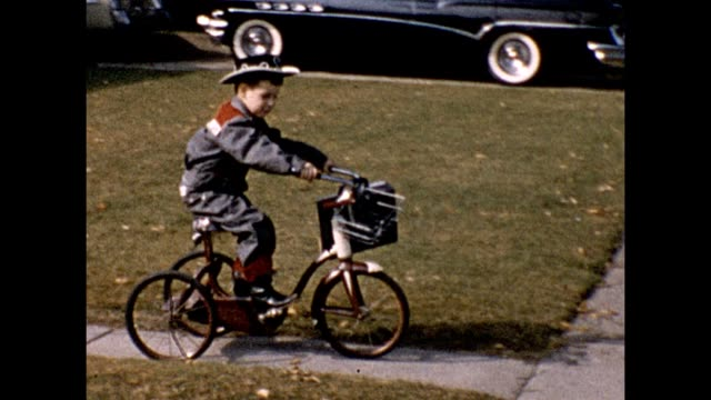 1957 boy in sheriff costume riding tricycle - tricycle stock videos & royalty-free footage