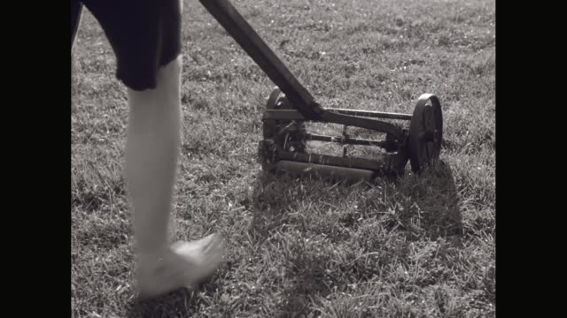 MS TS boy in shorts pushing lawnmower / United States