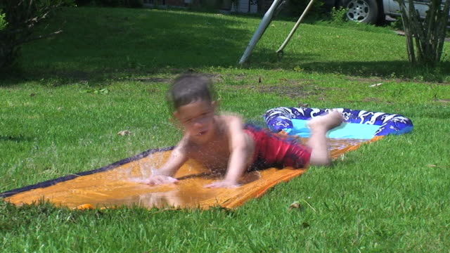 boy in summer - water slide stock videos & royalty-free footage