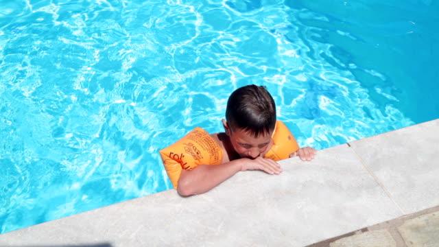 junge im schwimmbad, handheld erschossen - schwimmflügel stock-videos und b-roll-filmmaterial