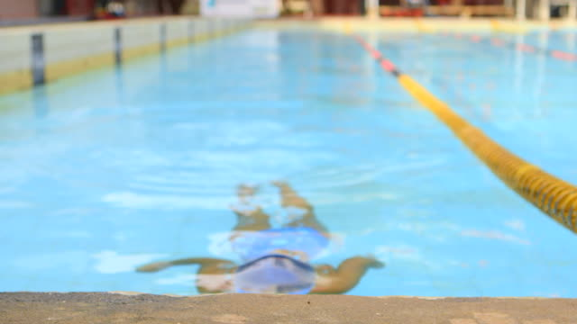 stockvideo's en b-roll-footage met close up handheld boy in swimsuit bathing cap and swimming goggles swims toward camera raises out of pool and smiles outdoors - alleen kinderen