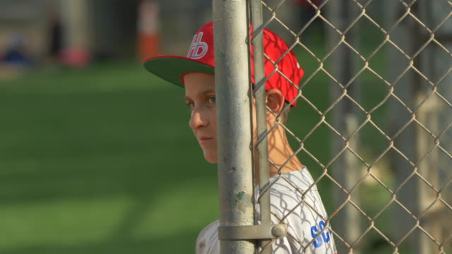 boy in the dugout at a little league baseball game. - slow motion - dugout stock videos & royalty-free footage