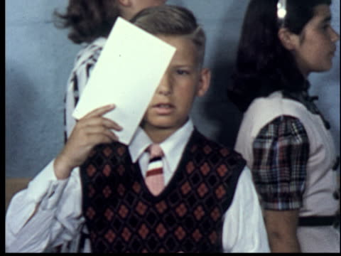 1955 MS Boy in vest and tie covering right eye with piece of paper for eye exam/ MS woman administering eye exam