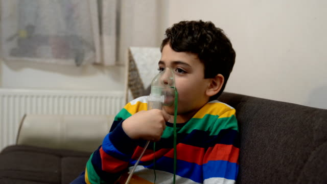 boy inhaling through inhaler mask - respiratory machine stock videos & royalty-free footage