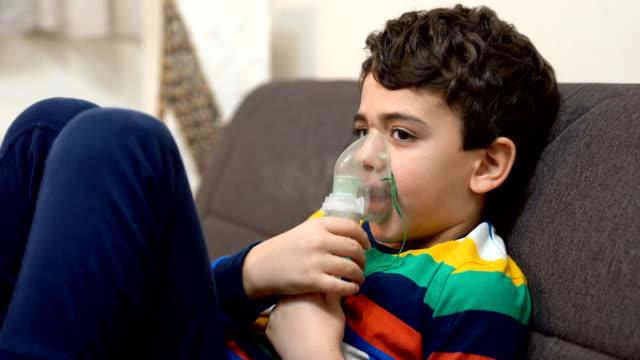 boy inhaling through inhaler mask - bronchiole stock videos & royalty-free footage