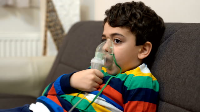 boy inhaling through inhaler mask - bronchi stock videos & royalty-free footage