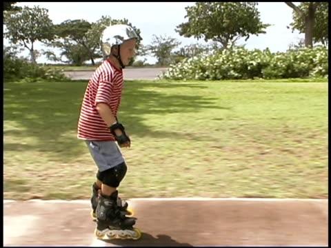 boy inline skating in park - 男児のみ点の映像素材/bロール
