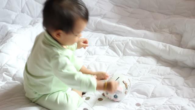 vidéos et rushes de garçon insérer pièces dans la tirelire en forme de cochon - tirelire