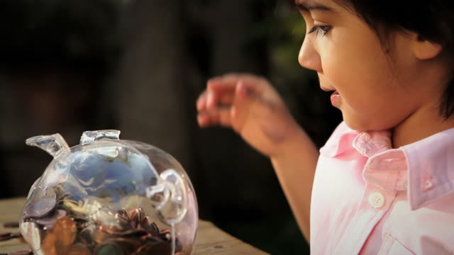 cu pan boy (2-3) inserting pennies in piggy bank / los angeles, california, usa - saving up for a rainy day stock videos and b-roll footage