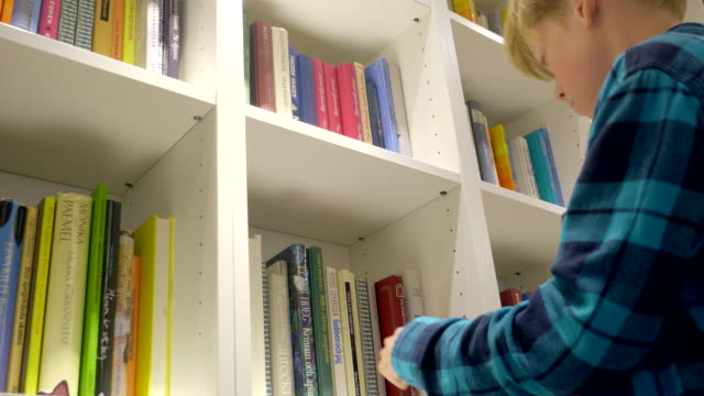boy is choosing a book at the bookshelf. - bookshelf stock videos & royalty-free footage
