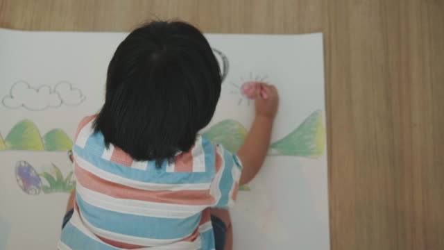 boy is drawing and crayon of dinosaur - crayon stock videos & royalty-free footage