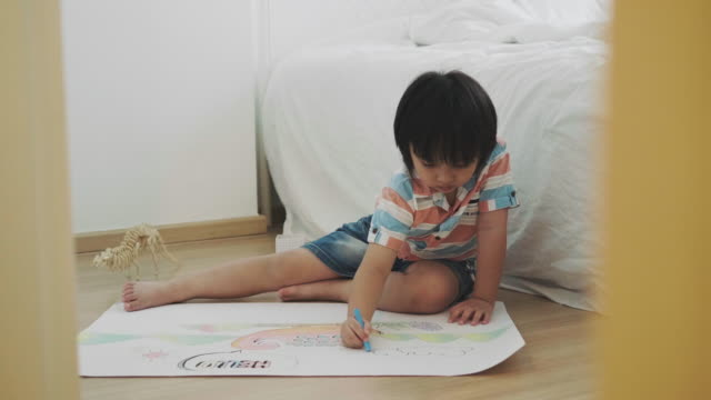 boy is drawing and crayon of dinosaur - crayon stock videos and b-roll footage
