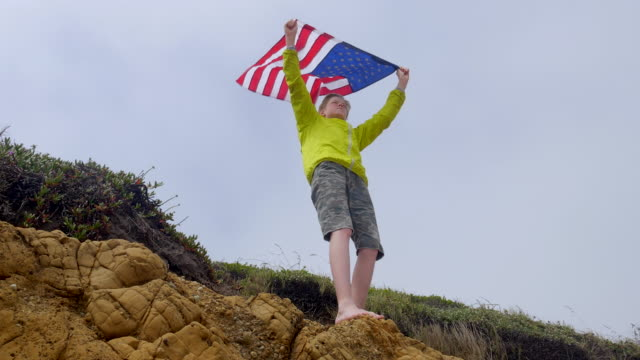 boy is holding waving american flag above his head on a rock. - pledge of allegiance stock videos & royalty-free footage