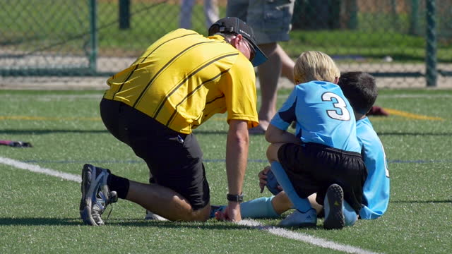 a boy is injured while playing injury youth soccer football on a turf field. - slow motion - injured stock videos & royalty-free footage
