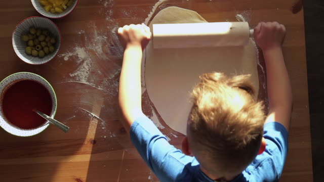 stockvideo's en b-roll-footage met boy is  kneading a pizza dough with a rolling pin - table top view