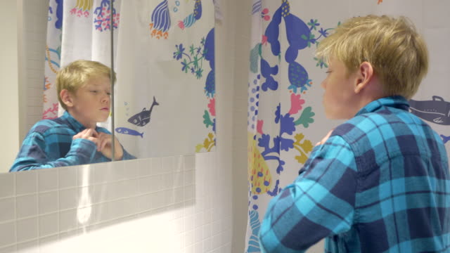 boy is looking in mirror, dressing up and preparing to go outside in the bathroom. - teenage boys stock videos & royalty-free footage