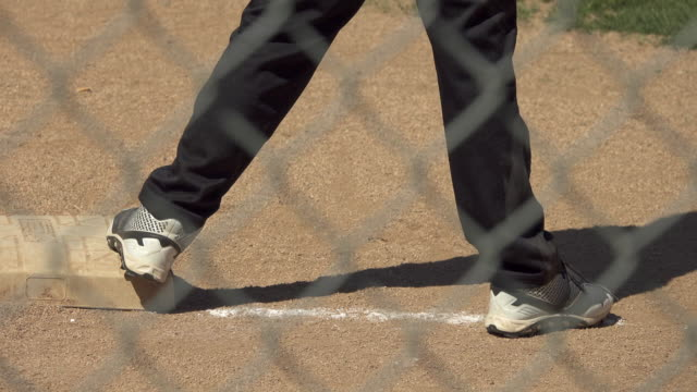 A boy is on base while playing in a little league baseball game.