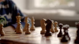Boy is playing chess in home