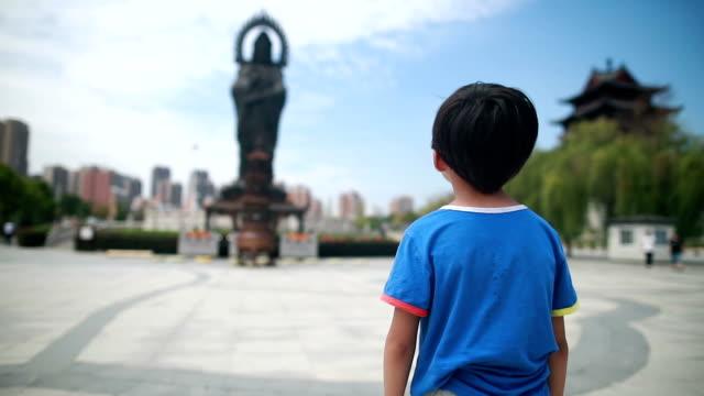 少年は、パゴダの仏像を祈っています。 - 人の背中点の映像素材/bロール