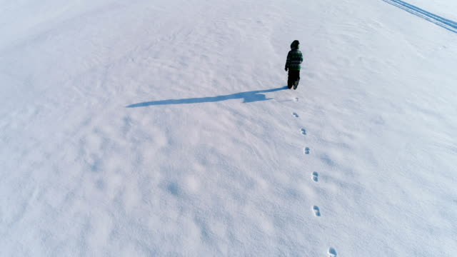 Boy is running on a snow covered area, laying on the snow and makes snow angel, aerial footage.