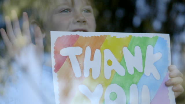 "boy is showing ""thank you"" drawing to doctors during quarantine for covid-19 - positive emotion stock videos & royalty-free footage"