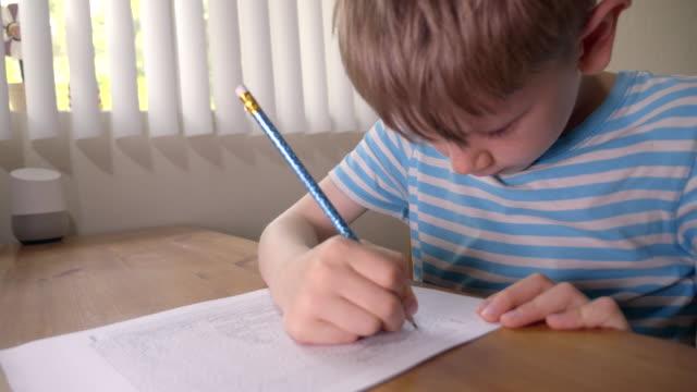 少年は自宅で鉛筆で紙の上に印刷された迷路を解いています。 - 迷路点の映像素材/bロール