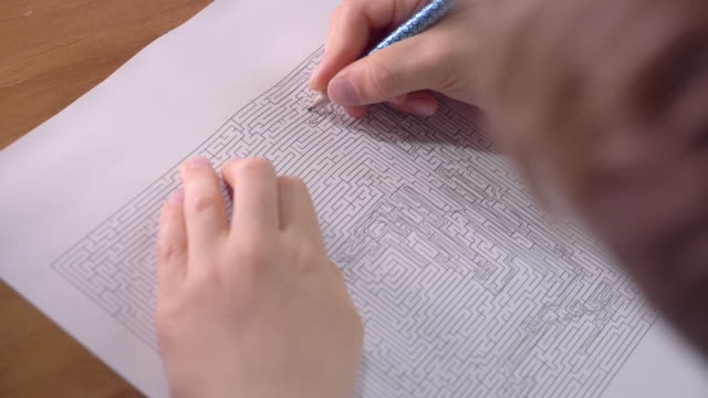 boy is solving printed labyrinth on paper with pencil at home. - maze stock videos & royalty-free footage