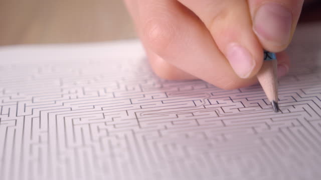 boy is solving printed labyrinth on paper with pencil at home. - decisions stock videos & royalty-free footage