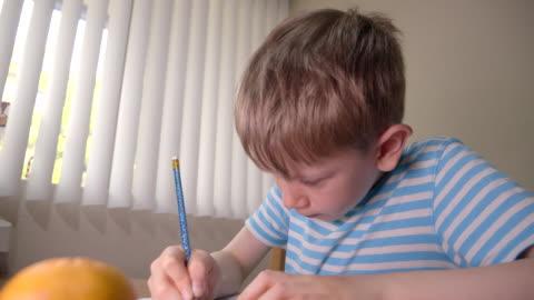 stockvideo's en b-roll-footage met boy is het oplossen van gedrukte labyrint op papier met potlood thuis. - chaos