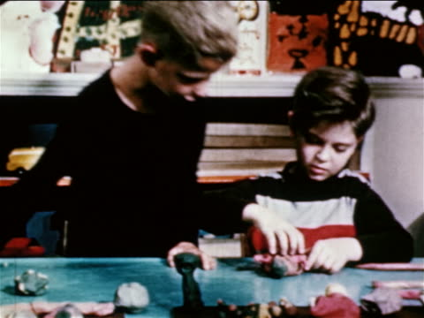 1950 boy joining another boy creating clay objects at table in classroom / educational - schoolboy stock videos and b-roll footage
