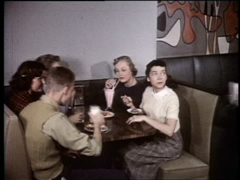 1954 boy joining group of teens at booth in malt shop - 1954 stock videos & royalty-free footage