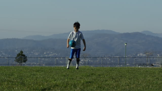 boy juggling soccer ball - jonglieren stock-videos und b-roll-filmmaterial