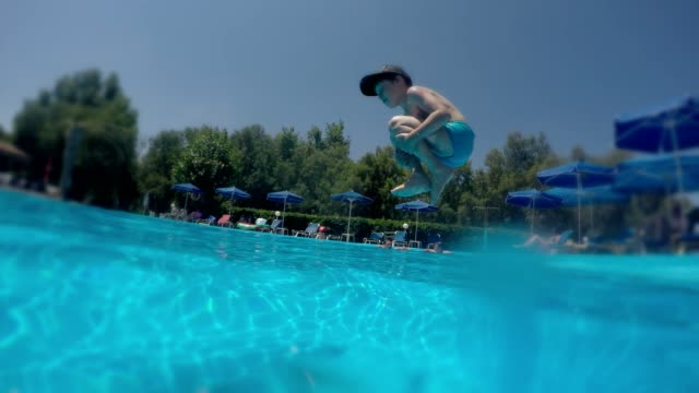 boy jump dive-bomb to pool - holiday villa stock videos & royalty-free footage