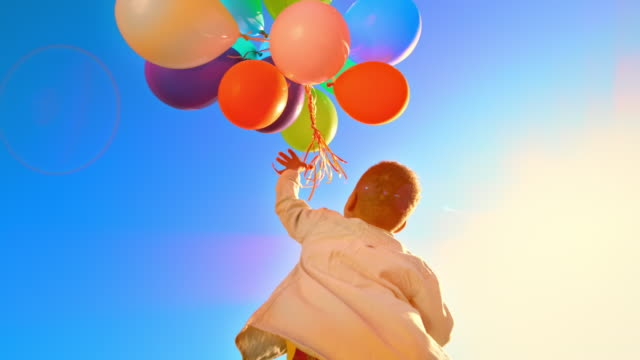 slo mo boy jumping and releasing a bunch of colourful balloons into the sky - releasing stock videos & royalty-free footage