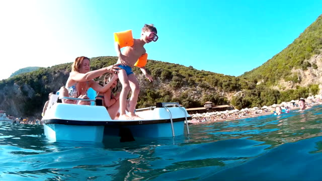 boy jumping from pedal boat - pedal boat stock videos and b-roll footage