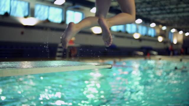 vídeos y material grabado en eventos de stock de boy jumping in indoors swimming pool - lanzarse al agua