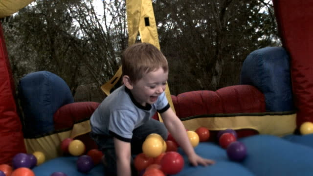 MS, SLO MO, Boy (2-3) jumping in inflatable jumping castle
