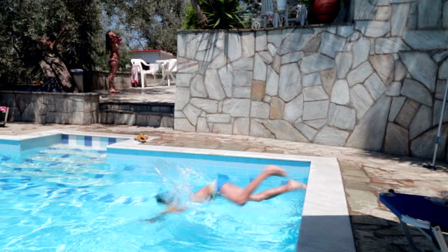 Boy jumping in swimming pool, handheld shot