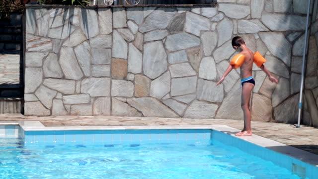 junge, springen im schwimmbad, handheld erschossen - schwimmflügel stock-videos und b-roll-filmmaterial